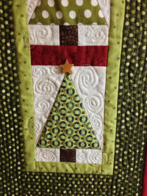 Quilting detail and wooden star bead embellishment.