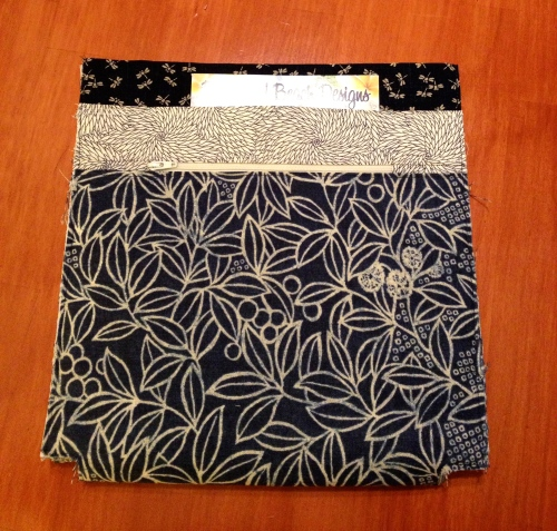 The outside front has a zippered pocket and a non-zippered pocket.